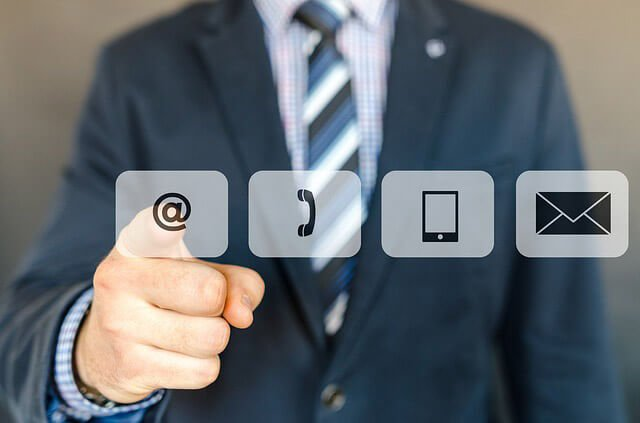 Man in a suit pointing to icons for various contact methods